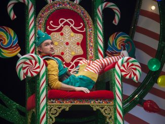 An elf sits on a throne.